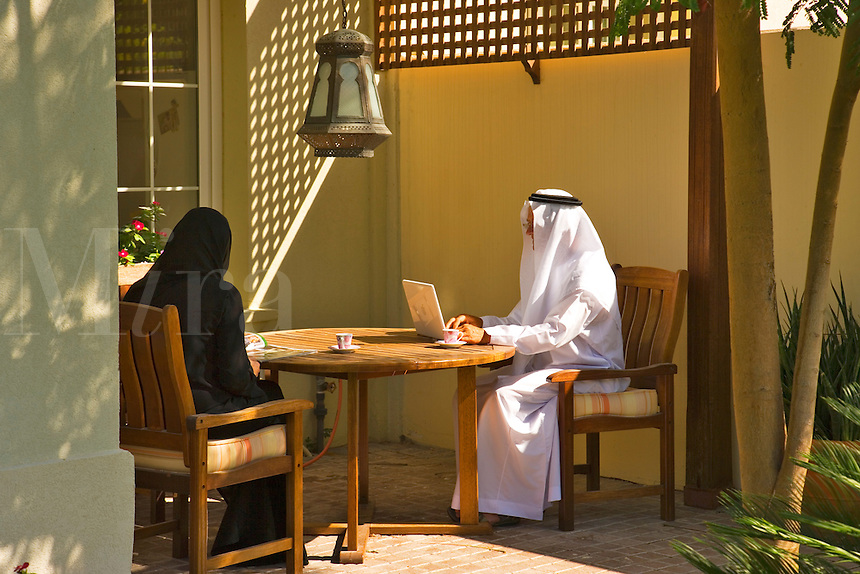 Dubai.  Traditionally dressed local Arab couple outside in their garden, the man works on his laptop computer..