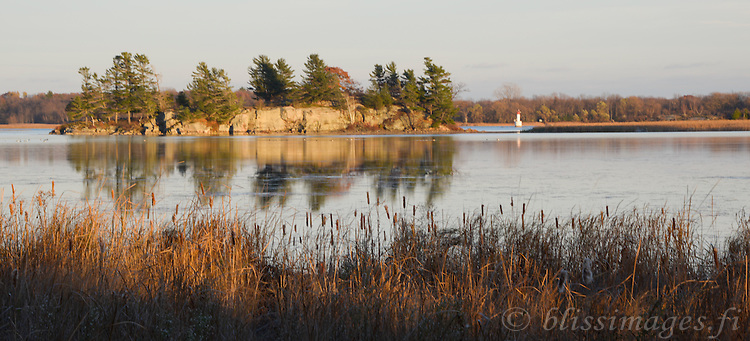 The late autumn sun sets over marshes, islands and a channel mark as seen from 1000 Islands Parkway in Southern Ontario.