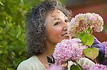 Asian woman smiling and smelling flowers