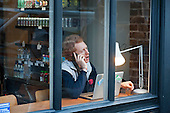 A man working on a laptop talks on a mobile phone in the window of a cafe with wi-fi access in Shoreditch, London, a run-down commercial district  also known as Silicon Roundabout, which is undergoing gentrification as it becomes a centre for web-based companies and IT start-ups.
