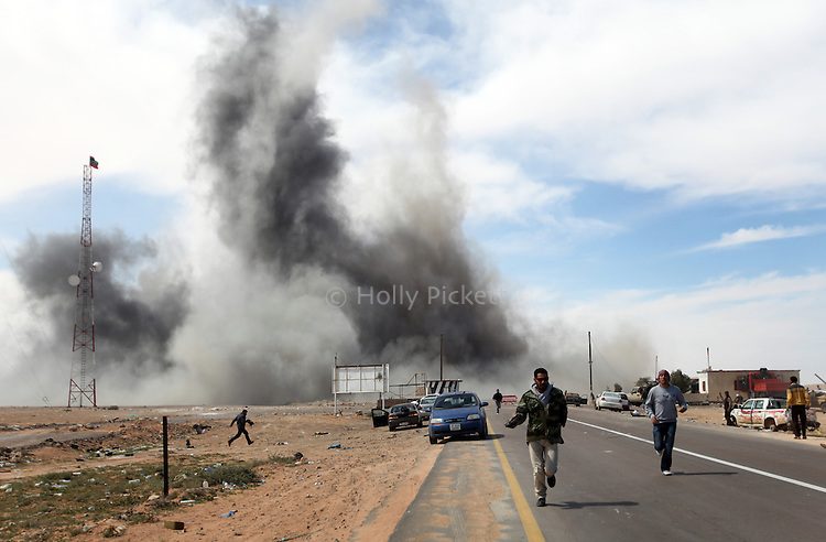 People run from an air strike on a rebel-held checkpoint near Al Uqaylah, Libya, March, 12, 2011. The rebels continued to lose ground against loyalist forces of Col. Muammar Qaddafi and were attacked from the air, the sea and the ground.