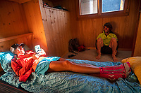 Friends reading and relaxing inside the Turtmann Hut, during the Via Valais, a multi-day trail running tour connecting Verbier with Zermatt, Switzerland.