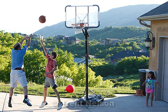 Salt Lake County - John Skedros fires a shot during a pre-dinner pickup game with Alex Millet in the Emigration Oaks neighborhood above Emigration Canyon Wednesday, June 18, 2008. The community has taken steps to reduce potential fire fuels and clear brush and trees that are too close to homes. At right is Angelina Skedros, watching.
