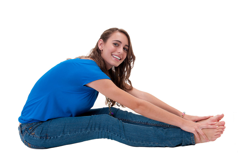 Young and happy caucasian woman, seated in the floor stretching.