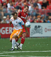 18 July 2009: Houston Dynamo midfielder Brian Mullan #9 and Toronto FC forward Chad Barrett #19 in action during a game between the Toronto FC and Houston Dynamo..The game ended in a 1-1 draw..