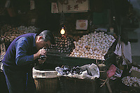 With the help of a light bulb provided for that purpose, a man examines an egg closely for freshness at an open air egg stall near Hong Kong Central's market.