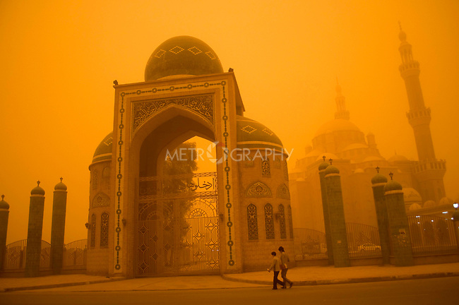 ERBIL, IRAQ: Two people walk in front of the Jalel Khayat Mosque during a massive sandstorm...The first sandstorm of the season hits northern Iraq...Photo by Metrography