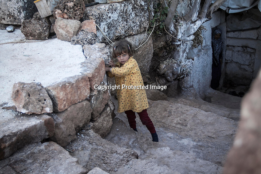 "In this Friday, Sep. 27, 2013 photo, a Syrian displaced little girl walks upstairs from her family cave house at the Kafr Ruma, an ancient roman ruins used as temporary shelter by those families who have fled from the heavy fighting and shelling in the Idlib province countryside of Syria. Dozens of families settled in the ancient ruins known as ""The Forgotten City"" and declared human heritage by UNESCO, when the clashes between opposition fighters and government forces broke out in the region since more than two years ago. (AP Photo)"