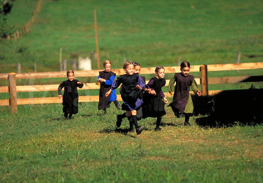 Amish girls running through a field. Amish girls. Strasburg Pennsylvania USA Lancaster County.