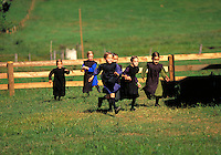 Amish girls running through a field. Amish girls. Strasburg Pennsylvania USA Lancaster County.