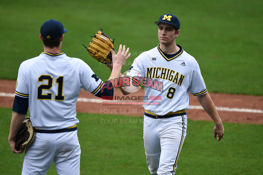 Michigan Wolverines pitcher Ryan Nutof (8) is greeted by Evan Hill (12) on his way to the dugout during the first game of a doubleheader against the Siena Saints on February 27, 2015 at Tradition Field in St. Lucie, Florida.  Michigan defeated Siena 6-2.  (Mike Janes/Four Seam Images)