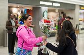A woman is given a bouquet of flowers as she arrives from Dubai after a 14-hour flight on Emirates flight 231, at the international terminal at Dulles International Airport in Dulles, Va., Monday, March16, 2020. Some people are taking the precaution of wearing face masks as they arrive to be greeted by family and or friends. Credit: Rod Lamkey / CNP