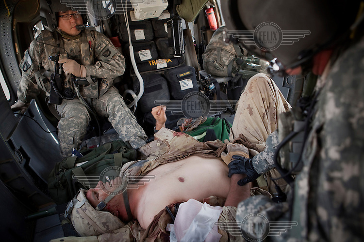 Medics from Charlie Company, Sixth Battalion, 101st Aviation Regiment treat a wounded Canadian soldier onboard a US Army medevac helicopter near Kandahar. He was wounded by shrapnel to his arm.