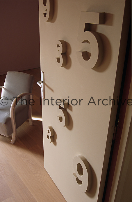 A door decorated in numbers of various sizes opens to reveal a simply upholstered armchair