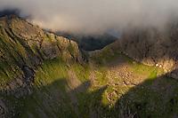 Mountain peaks cast shadows on distant hillside, Moskenesøy, Lofoten Islands, Norway