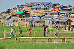 People walk across a rickety bridge over a flooded rice paddy in the Jamtoli Refugee Camp near Cox's Bazar, Bangladesh. More than 600,000 Rohingya have fled government-sanctioned violence in Myanmar for safety in Bangladesh.