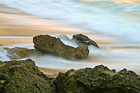 wind and waves sweep over the beach's sand and rocks under beautiful clouds and sunset
