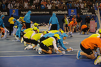 MELBOURNE, 29 JANUARY - Ball kids dry the court surface after rain halted play at the men's finals match on day 14 of the 2012 Australian Open at Melbourne Park, Australia. (Photo Sydney Low / syd-low.com)