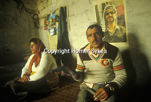 PLO, Palastine Liberation Organisation camp Lebanon 1980s, man with wife in their home, he s prowdly showing me his gun. On the wall behind is a poster of Yasser Arafat. Middle East.