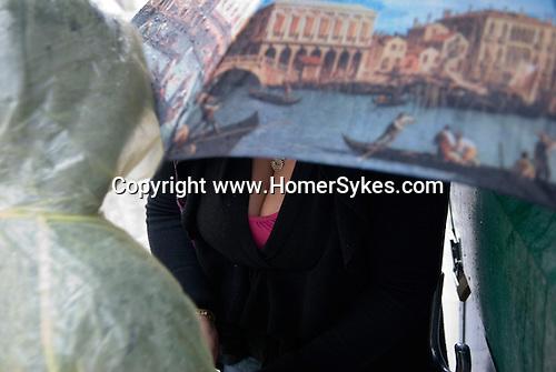 Venice Italy 2009. Tourist with Venice umbrella in rain.