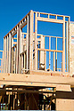 The second story of a single family home beginning to take shape. The building of this large home requires huge amounts of wood and other raw materials. A single-story home used to occupy the lot. Cupertino, California, USA