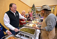 STAFF PHOTO BEN GOFF  @NWABenGoff -- 12/25/14 Randy Brucker, left, of Rogers serves green beans to Perry Schaffer of Cave Springs during the annual Christmas meal for the community at Central United Methodist Church in Rogers on Thursday Dec. 25, 2014. The church and volunteers from the community also offer take out dinners and delivery for homebound individuals on Christmas.
