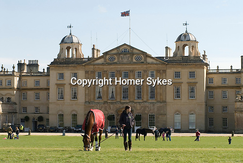 Badminton Horse Trials Gloucestershire UK.Badminton House competitors grazing horse in front of house.