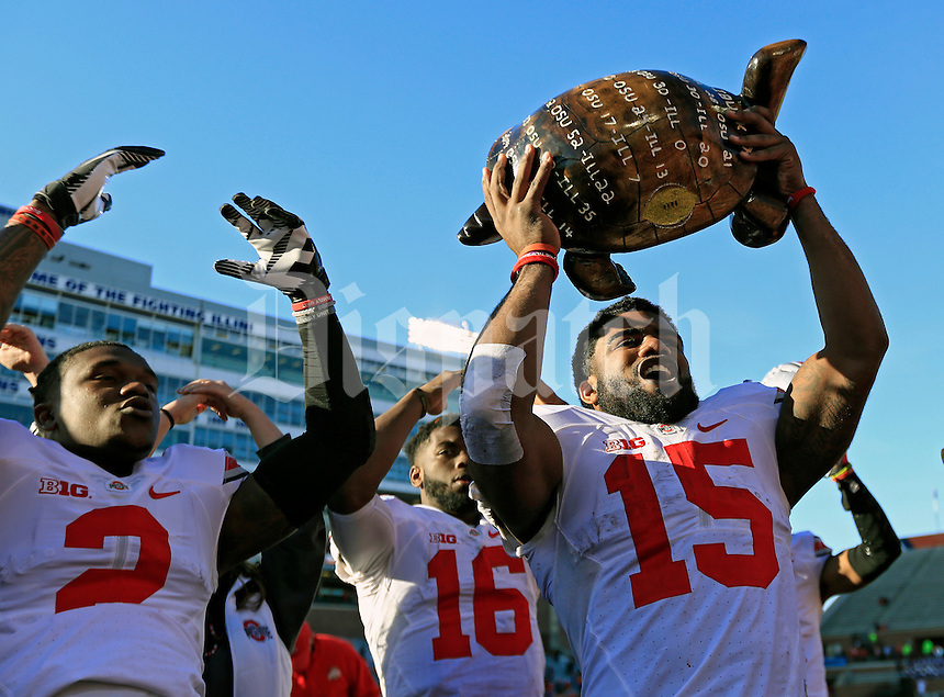 Ohio State Buckeyes running back Ezekiel Elliott (15) holds up the Illibuck Trophy while singing Carmen Ohio after Ohio State Buckeyes beat Illinois Fighting Illini 28-3 in their game at Memorial Stadium in Champaign, IL on November 14, 2015.  (Dispatch photo by Kyle Robertson)