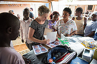 Occidental College professor Mary Beth Heffernan hands out completed portrait prints as she works on her PPE Portrait Project with health care workers at the ELWA II ETU (Ebola treatment unit) in Monrovia, Liberia on Tuesday, March 3, 2015. The ETU, operated by ELWA Hospital, was the first to open in Monrovia. Professor Heffernan's project involves creating wearable portraits of health care workers who must wear PPE (personal protective equipment) when working with patients, for example, patients with Ebola. <br /> (Photo by Marc Campos, Occidental College Photographer) Mary Beth Heffernan, professor of art and art history at Occidental College, works in Monrovia the capital of Liberia, Africa in 2015. Professor Heffernan was there to work on her PPE (personal protective equipment) Portrait Project, which helps health care workers and patients fighting the Ebola virus disease in West Africa.<br />