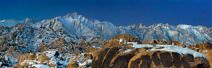 902000014 a panoramic view of dawn light on mount whitney mount russell and lone pine peak during a clearing snowstorm with a dusting of fresh snow on the eastern sierras and the granite boulders of the alabama hills in the blm protected lands near lone pine kern county california