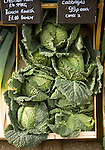 Fresh cabbages on display in wooden crate box