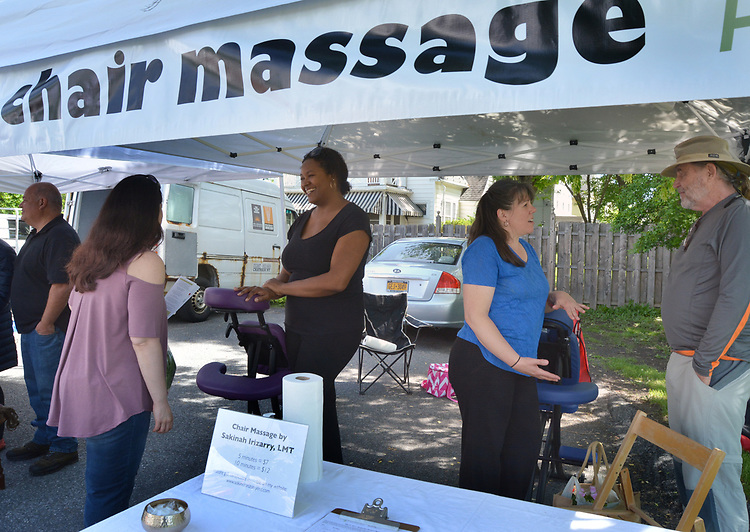 Customers visiting Licensed Massage Therapist, Sakinah Irizarry, at her Chair Massage booth, at the Opening Day of the 2017 Saugerties Farmer's Market on Saturday, May 27, 2017. Photo by Jim Peppler. Copyright/Jim Peppler-2017.
