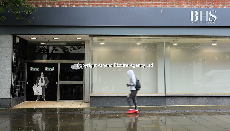 Pictured: A man walks past a poster of Sir Philip Green on the door of the now closed down BHS store in Oxford Street, Swansea, Wales, UK. Tuesday 13 September 2016<br /> Re: Former owner of BHS, Sir Philip Green has paid a surprise 'visit' to the closed down BHS store in Swansea.<br /> He was spotted in the doorway of the Oxford Street store, which closed its doors for the last time last month.<br /> In his hand was a BHS shopping bag with money spilling out of it.<br /> Sir Philip had owned BHS before selling it for &pound;1 last year.<br /> He is claimed to have taken millions out of the company in dividends and left behind a &pound;571m pensions deficit.<br /> Alongside the poster are the words: &quot;Thankyou for your custom Sir&quot;.