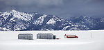 Bonneville County, Idaho: Metal silos and red barn in open field with snow and storm clouds