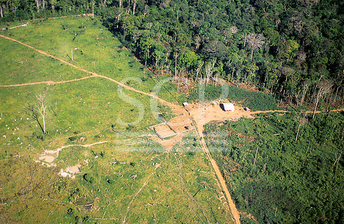 Amazon, Brazil. Aerial view of settler's house on cleared rainforest land with dirt roads, poor pasture and animal pens.