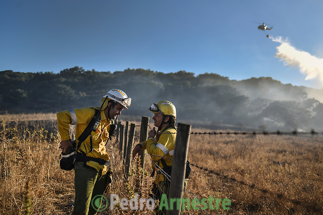 The firefighters from the BRICA, the Andalusian Service firefighting (INFOCA), expect the helicopter to return to base after a forest fire in Los Barrios, near Cadiz on July 25, 2015. Since July 19 wildfires have ravaged nearly 39,000 hectares of land in Spain, according to the provisional figures from the agriculture ministry. © Pedro ARMESTRE