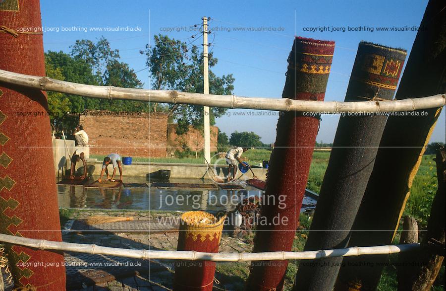INDIA Uttar Pradesh, Badohi, worker wash carpets at carpet manufacture in a village in the carpetbelt between Badohi and Mirzapur / INDIEN, Arbeiter waschen Teppiche in einer kleinen Manufaktur in einem Dorf