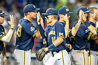 Michigan Wolverines third baseman Blake Nelson (10) celebrates with this teammates following Game 6 of the NCAA College World Series against the Florida State Seminoles on June 17, 2019 at TD Ameritrade Park in Omaha, Nebraska. Michigan defeated Florida State 2-0. (Andrew Woolley/Four Seam Images)