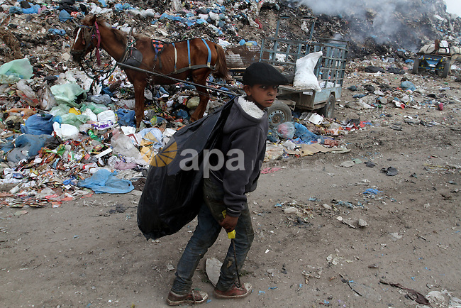 A Palestinian boy carries recyclables collected from the garbage near the border with Israel, east of Rafah town, in the southern Gaza Strip, April 16, 2015. Workers collect the household recyclables, metals and plastic from landfill and garbage to sell to the Israeli and local factories. Photo by Abed Rahim Khatib