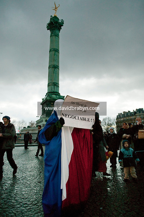 """A muslim woman wearing a full head-to-toe chador made out of the French red-white-and-blue flag holds up a sign in French that reads """"my freedom of religion is not negotiable"""" during a street protest held in Paris, France, 21 December 2003, against a law that plans to restrict the wearing of veils in public schools."""