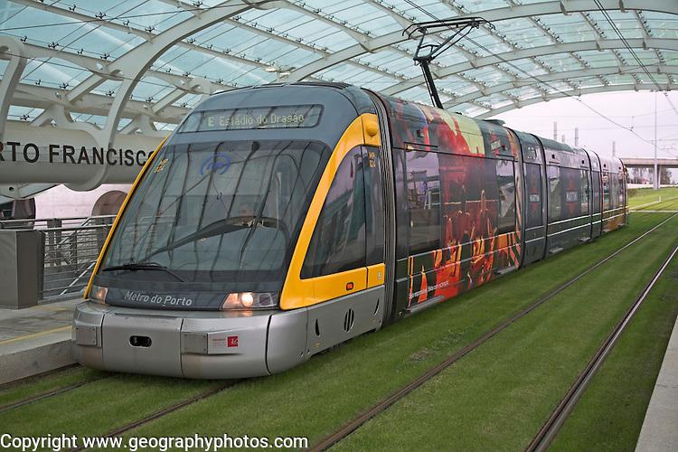 Metro train on grass tracks Oporto airport station, Porto, Portugal