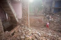 An elder woman walks to her tent through the rubble. Shanku, near Kathmandu, Nepal. May 9, 2015
