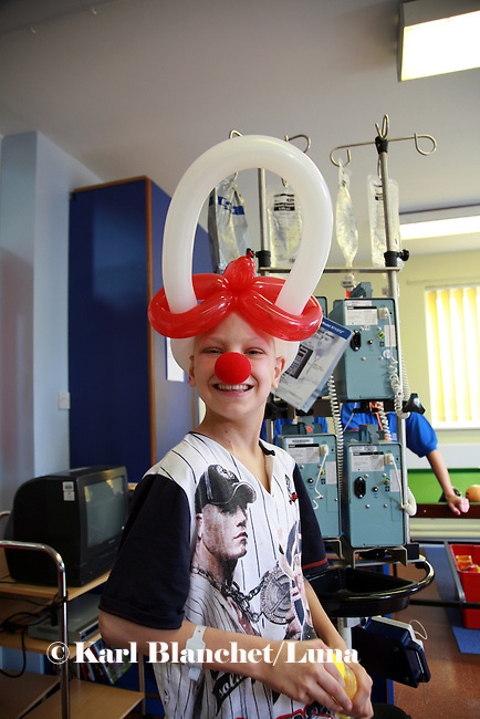 Jamie receives a red nose from the clowns as a recognition of his skills as a magician. Oncology ward at the Royal Manchester Children hospital.