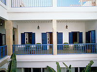 The riad's second floor terrace has blue wooden shutters on all the doors and windows and a matching balustrade