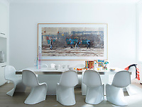 The family dining area is dominated by the large, steel edged table surrounded by classic Verner Panton dining chairs. The blue of the artwork on the wall provides a spot of colour to the otherwise white room.