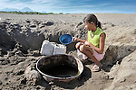 A girl obtains water by digging into a riverbed near Santa Paula, a hot and isolated village in northwestern Nicaragua.