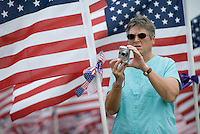 A woman photographs a field of 3,000 flags installed in a wheat field in Maria Stein, Ohio, Monday, September 11, 2006. The display was erected to honor military, police, fire fighters, and emergency workers on the anniversary of the attacks on the World Trade Center and Pentagon in 2001.<br />