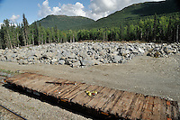 An old flatcar is parked in front of granite used for ballast under the railroad tracks. The Alaska Railroad's Denali Star train runs between Anchorage and Fairbanks, with Denali one of the stops along the way.