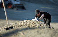 Pictured: An officer rests a forensics tag on one of the piles of soil before it is searched through by in Kos, Greece. Thursday 06 October 2016<br />