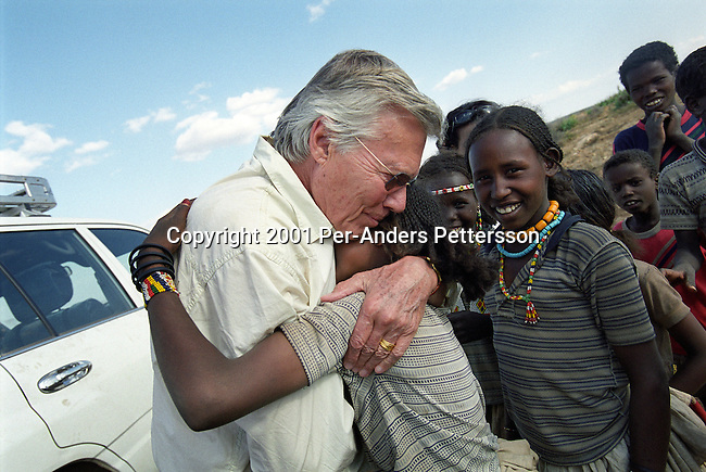 HARAR, ETHIOPIA FEBRUARY 7: Austrian actor KarlHeinz Bohm meets young girls as he visits an opening of a water project for several villages in a rural area February 7, 2001 outside Harar, Ethiopia. He Bohm has a house and runs his aid organization 'Menschen for Menschen in the area. Mr. Bohm runs several projects around the country and he is a popular man in the country. (Photo by Per-Anders Pettersson/Getty Images)